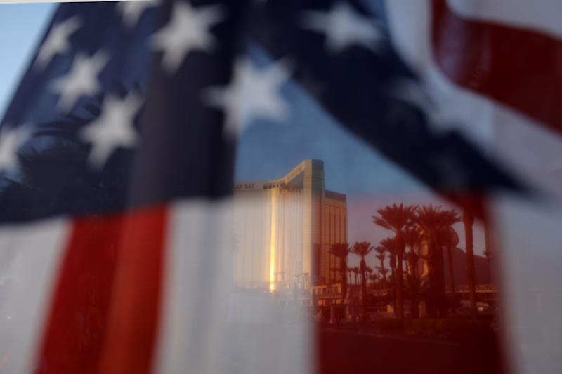 The Mandalay Bay hotel is shown through an American flag blowing in the wind at a memorial next to the mass shooting site along the Las Vegas Strip in Las Vegas, Nevada, U.S., October 4, 2017. (Mike Blake / Reuters)