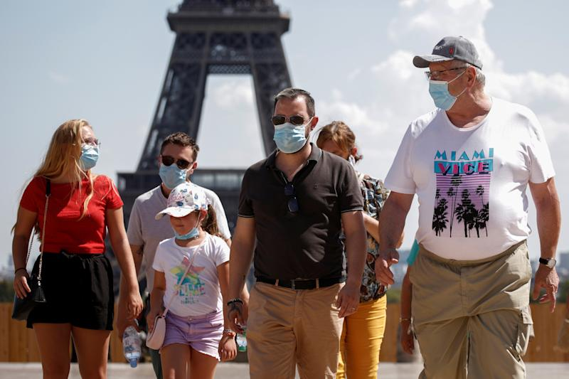 People wearing protective face masks walk at the Trocadero square near the Eiffel Tower in Paris as France reinforces mask-wearing as part of efforts to curb a resurgence of the coronavirus disease (COVID-19) across the country, August 9, 2020. REUTERS/Benoit Tessier