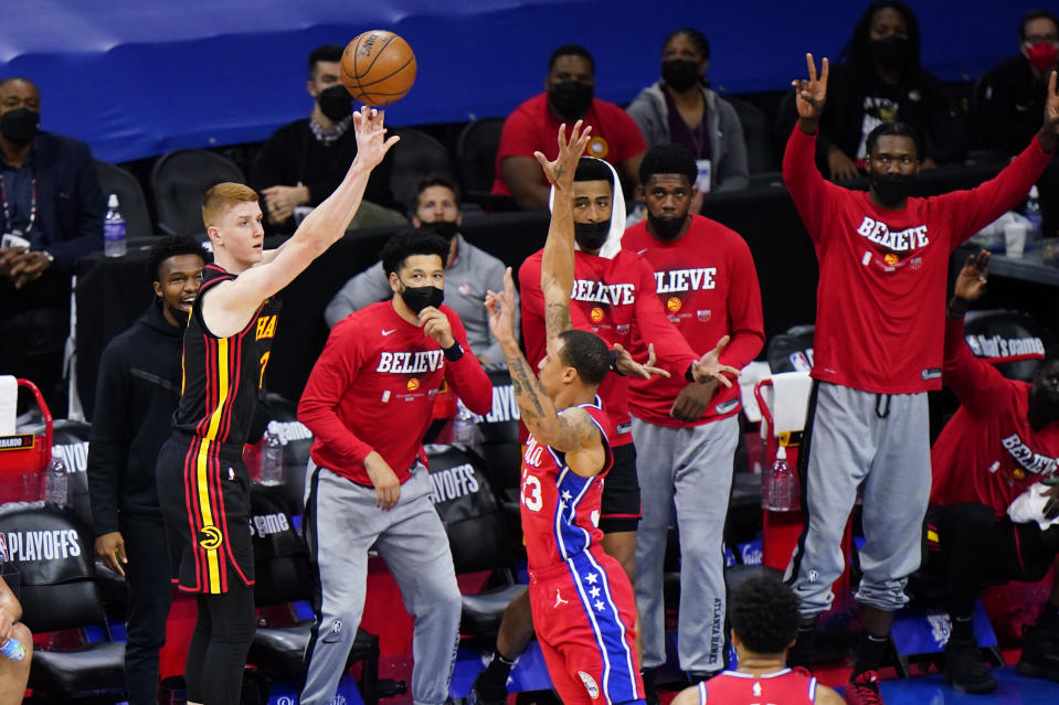 Atlanta Hawks' Kevin Huerter, left, goes for a shot against Philadelphia 76ers' George Hill during the first half of Game 1 of a second-round NBA basketball playoff series, Sunday, June 6, 2021, in Philadelphia. (AP Photo/Matt Slocum)