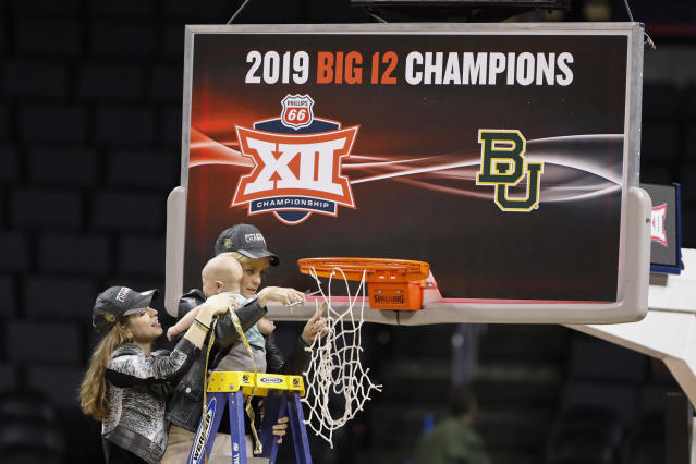 Baylor head coach Kim Mulkey holds her grandson, assisted by her daughter Makenzie Fuller, as she cuts down the nets after Baylor defeated Iowa State during the Big 12 women's conference tournament championship in Oklahoma City, Monday, March 11, 2019. Baylor won 67-49. (AP Photo/Alonzo Adams)