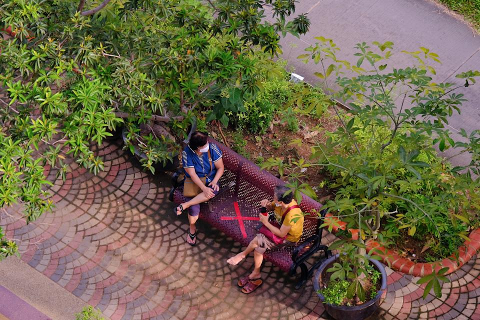 Singapore Sep2020 Two women in neighbourhood wearing protective face masks, observing social distancing in public. Public bench taped with a cross; covid-19 coronavirus lockdown