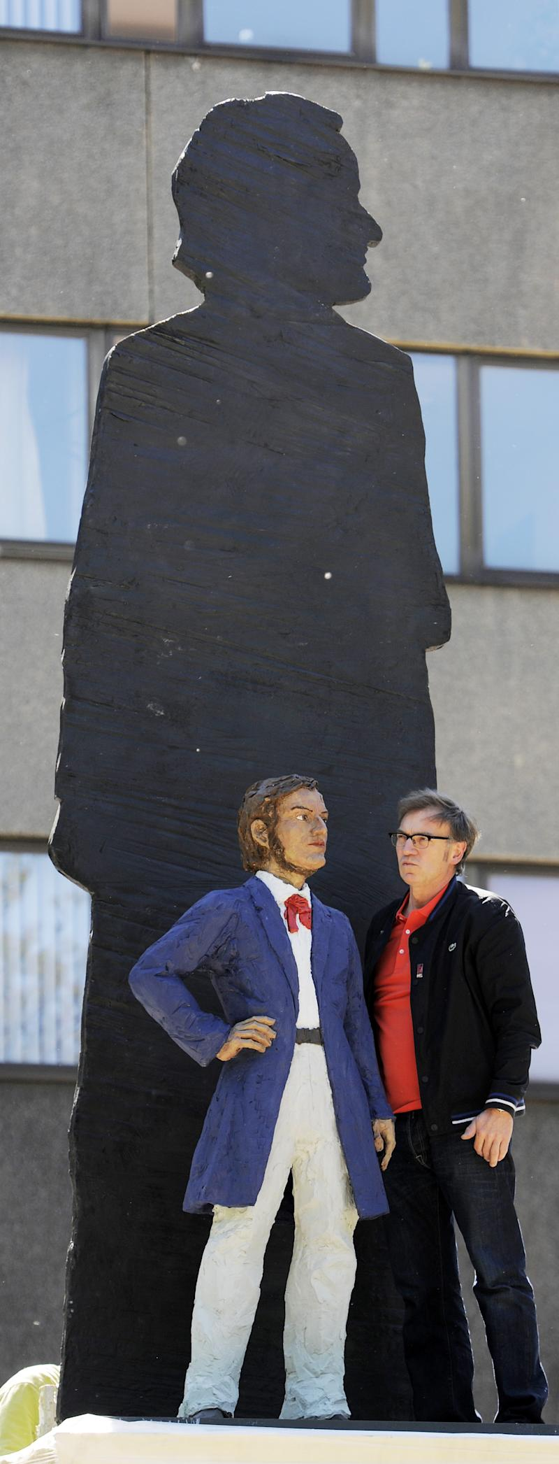 FILE - In this May 15, 2013 file photo German artist Stephan Balkenhol, right, stands besides a part of his Richard Wagner Monument during the installation in Leipzig, central Germany. The Wagner monument will be unveiled Wednesday, May 22, 2013, to celebrate the German composer's 200th birthday. It shows a young Wagner overshadowed by his older, famous self. Some of Wagner's works will be performed later in the day in Bayreuth, where the composer's descendants organize an annual music festival. (AP Photo/Jens Meyer, File)