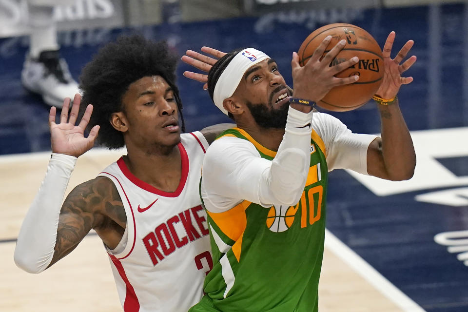 Utah Jazz guard Mike Conley (10) lays the ball up as Houston Rockets guard Kevin Porter Jr. (3) defends during the second half of an NBA basketball game Friday, March 12, 2021, in Salt Lake City. (AP Photo/Rick Bowmer)