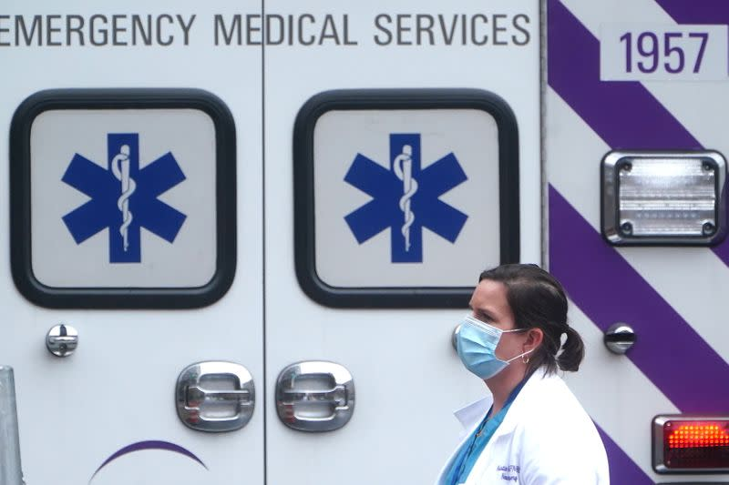 A health care professional walks past an ambulance during the coronavirus disease (COVID-19) pandemic in the Manhattan borough of New York City