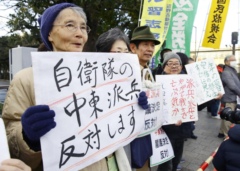 """People hold placards protesting against a troop dispatch to Middle East outside the prime minister's official residence in Tokyo Friday, Dec. 27, 2019. Japan on Friday approved a contentious plan to send its naval troops to the Middle East to contribute to the peace and stability in the area and ensure the safety of Japanese ships transporting oil, a mission crucial to an energy-poor country that heavily depends on oil imports from the region. The placard at left reads: """"Oppose a dispatch of Japan Self-Defense Forces to Middle East."""" (Hiroki Yamauchi/Kyodo News via AP)"""