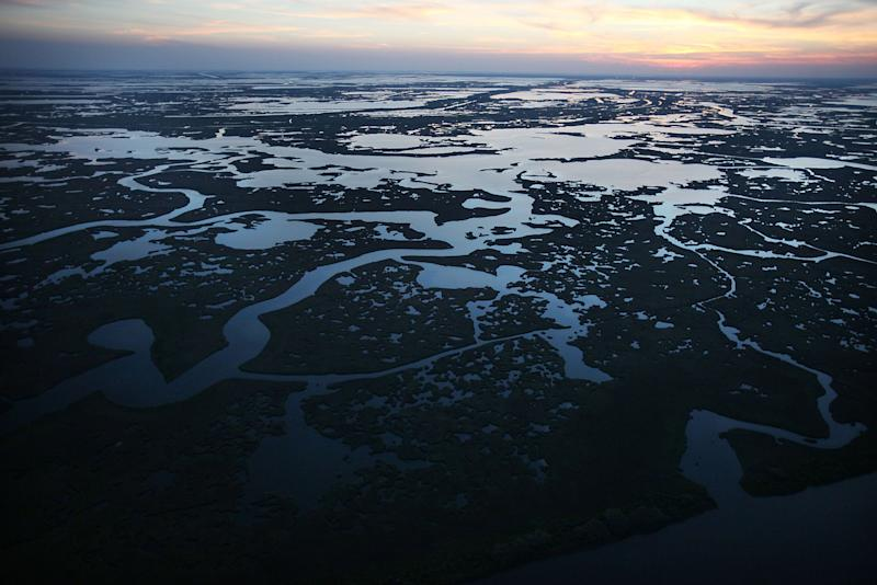 The sun sets over wetlands in Louisiana's Barataria Bay on April 13, 2011. Barataria Bay's fragile wetlands were among the hardest-hit in the aftermath of the Deepwater Horizon rig explosion, which spilled 206 million gallons of oil into the Gulf of Mexico in 2010. (Photo: Mario Tama/Getty Images)