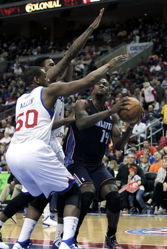 Charlotte Bobcats' Michael Kidd-Gilchris (14) looks to shoot as Philadelphia 76ers' Lavoy Allen (50) and Dorell Wright (4) defend in the first half of an NBA basketball game, Saturday, March 30, 2013, in Philadelphia. (AP Photo/H. Rumph Jr)