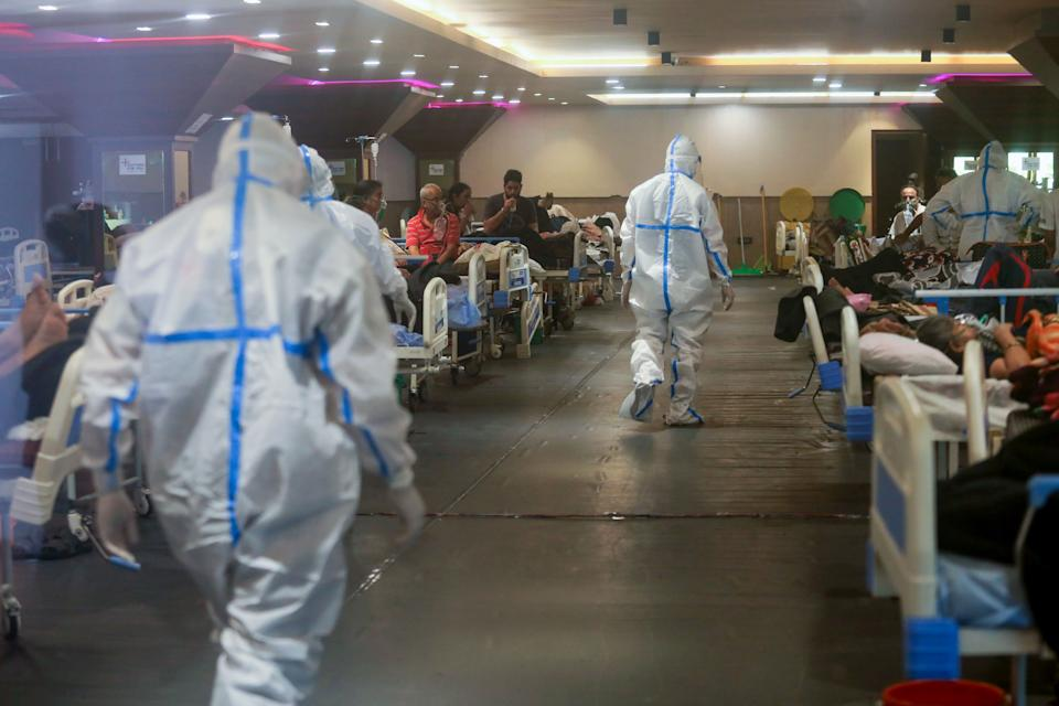 Healthcare workers in personal protective equipment (PPE) walk in the Covid-19 isolation ward. A banquet hall temporarily converted to a Covid19 ward for coronavirus patients. India has recorded the highest single-day spike in coronavirus infection. The report recorded 352,991 new Covid-19 cases and 2,812 people deaths in the last 24 hours amid an oxygen crisis. (Photo by Naveen Sharma / SOPA Images/Sipa USA)