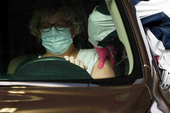 Hamilton County Health Department worker Shelly Donahue gives a shot of the COVID-19 vaccine to a woman on Wednesday at a drive-thru vaccination site in Chattanooga, Tenn.