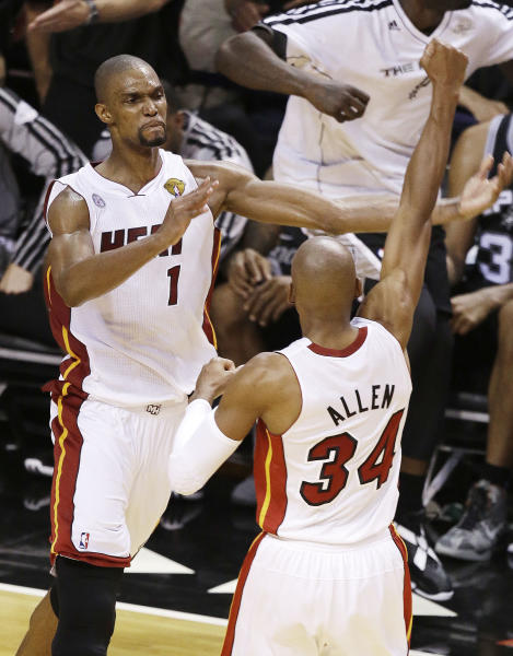 Miami Heat center Chris Bosh (1) and Miami Heat shooting guard Ray Allen (34) celebrate after overtime of Game 6 of the NBA Finals basketball game against the San Antonio Spurs, Wednesday, June 19, 2013 in Miami. The Heat defeated the Spurs 103-100. (AP Photo/Wilfredo Lee)