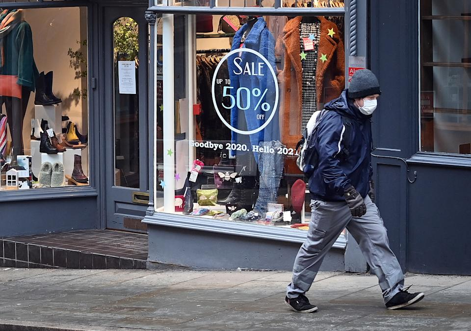 A pedestrian wearing a face mask or covering due to the COVID-19 pandemic, walks past a shop, temporarily closed down due to current coronavirus restrictions, in Shrewsbury, western England on January 6, 2021, on the second day of Britain's national lockdown to combat the spread of COVID-19. - England went back into full lockdown as Europe battled Wednesday to stem a rising tide of coronavirus cases, and the United States logged its worst daily death toll of the pandemic. (Photo by Paul ELLIS / AFP) (Photo by PAUL ELLIS/AFP via Getty Images)
