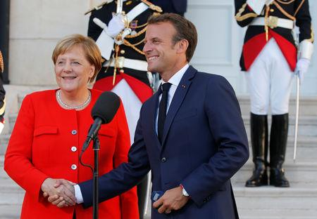 French President Emmanuel Macron and German Chancellor Angela Merkel shake hands before a meeting at the Pharo Palace in Marseille