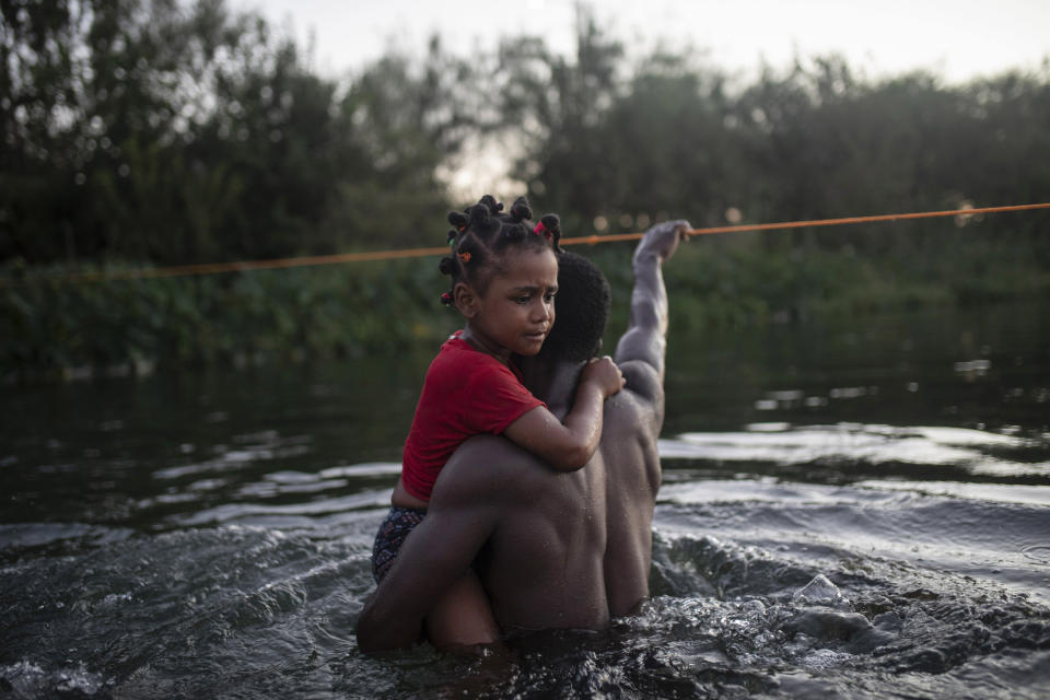 Haitian migrants wade across the Rio Grande from Del Rio, Texas, to return to Ciudad Acuña, Mexico, Sunday, Sept. 19, 2021, to avoid deportation to Haiti from the U.S. The U.S. is flying Haitians camped in a Texas border town back to their homeland and blocking others from crossing the border from Mexico in a massive show of force that signals the beginning of what could be one of America's swiftest, large-scale expulsions of migrants or refugees in decades. (AP Photo/Felix Marquez)