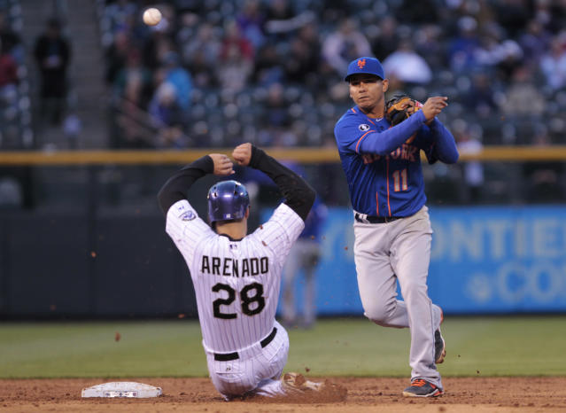 New York Mets shortstop Ruben Tejada (11) throws to first base after forcing out Colorado Rockies' Nolan Arenado (28) on a double play in the third inning of a baseball game in Denver, Thursday, May 1, 2014. Rockies' Carlos Gonzalez was out at first base. (AP Photo/Joe Mahoney)
