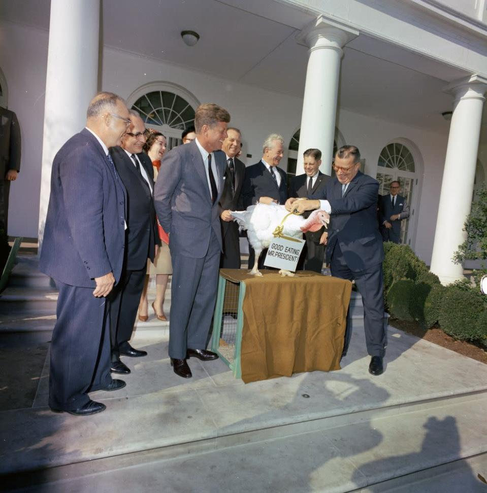 """<p>In 1963, President Kennedy received this turkey from the National Turkey Federation. It wore a sign around its neck that read, """"Good Eating, Mr. President!"""" But it seems JFK had a soft spot for his new feathered friend and sent it back to the farm from whence it had come. """"We'll just let this one grow,"""" he said. <i>(Photo: John F. Kennedy Library Presidential Library and Museum/NARA)</i></p>"""