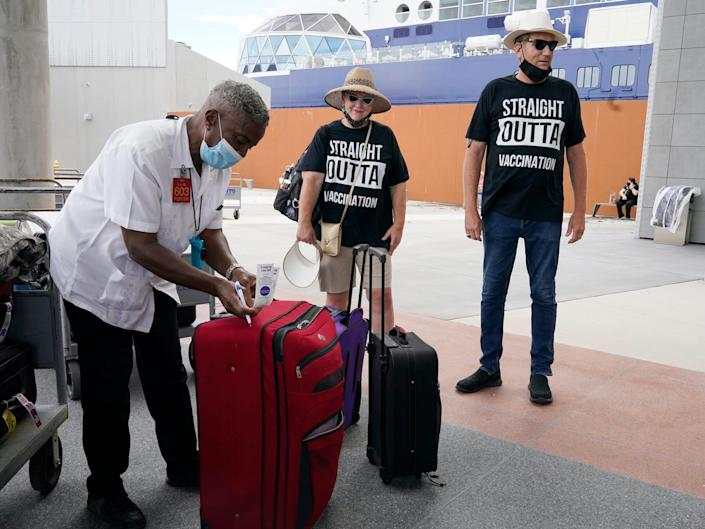 a cruise worker tagging the bags of two passengers standing nearby