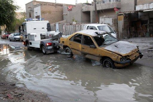 An Iraqi police truck tows away a taxi after it was damaged in  Baghdad, December 31, 2012