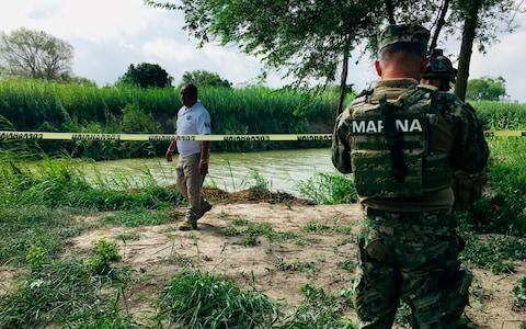 Mexican authorities walk along the Rio Grande bank where the bodies of Salvadoran migrant Oscar Alberto Martinez Ramirez and his nearly 2-year-old daughter Valeria - Credit: Julie Le Duc