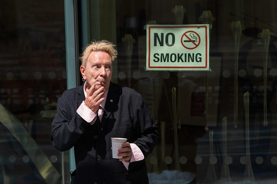 John Lydon, aka Johnny Rotten, smokes outside the Rolls Building at the High Court on Wednesday (PA)