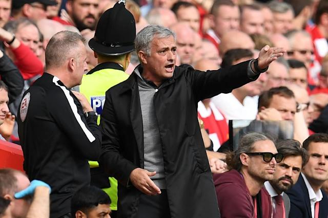 Manchester United's manager Jose Mourinho (R) speaks with fourth official, English referee Jonathan Moss during their English Premier League match against Liverpool at Anfield in Liverpool, north west England on October 14, 2017 (AFP Photo/Paul ELLIS)