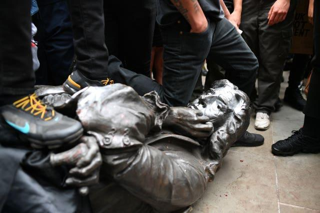 The Edward Colston statue at the feet of protesters (Ben Birchall/PA)