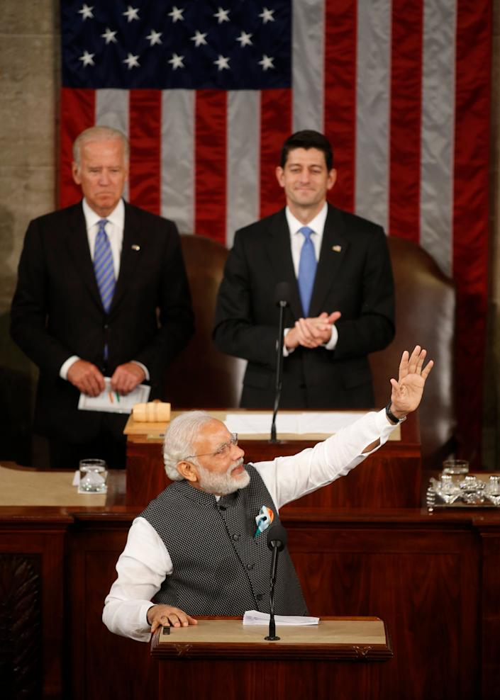 Vice President Joe Biden, left, and Speaker of the House Paul Ryan look on as India Prime Minister Narendra Modi acknowledges applause as he arrives to address a joint meeting of Congress in the House chamber on Capitol Hill in WashingtononJune 8, 2016.