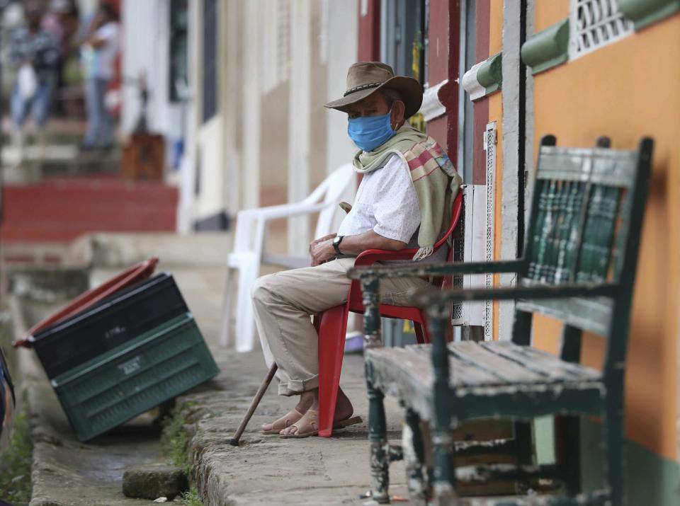 Wearing a mask to curb the spread of the new coronavirus, a man sits on his front porch in Campohermoso, Colombia, Thursday, March 18, 2021. According to the Health Ministry, Campohermoso is one of two municipalities in Colombia that has not had a single case of COVID-19 since the pandemic started one year ago. (AP Photo/Fernando Vergara)