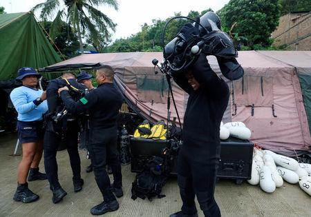 Rescue team members prepare their diving gear before a search operation for the missing passengers after a ferry sank earlier this week in Lake Toba in Simalungun, North Sumatra, Indonesia, June 23, 2018. REUTERS/Beawiharta