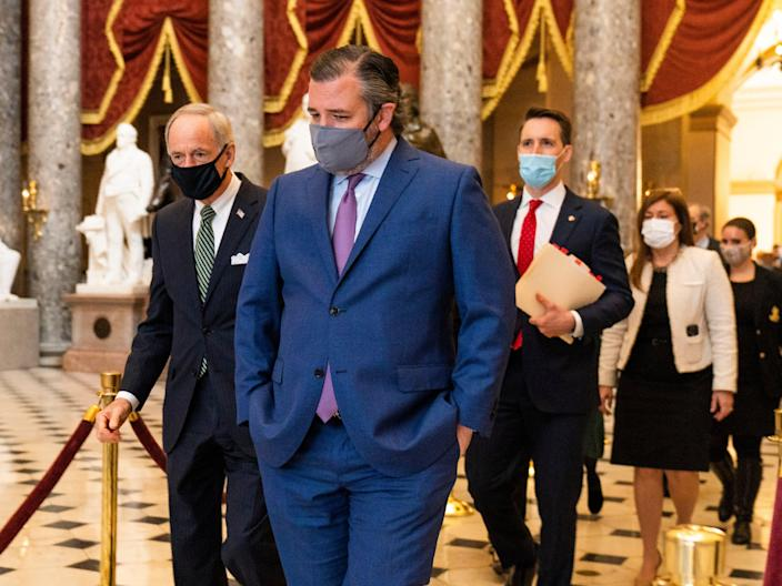 <p>Ted Cruz, front, followed by Josh Hawley, walk from the House Chamber following a Senate procession carrying boxes holding Electoral College votes to the House Chamber on Wednesday 6 January</p> ((Associated Press))