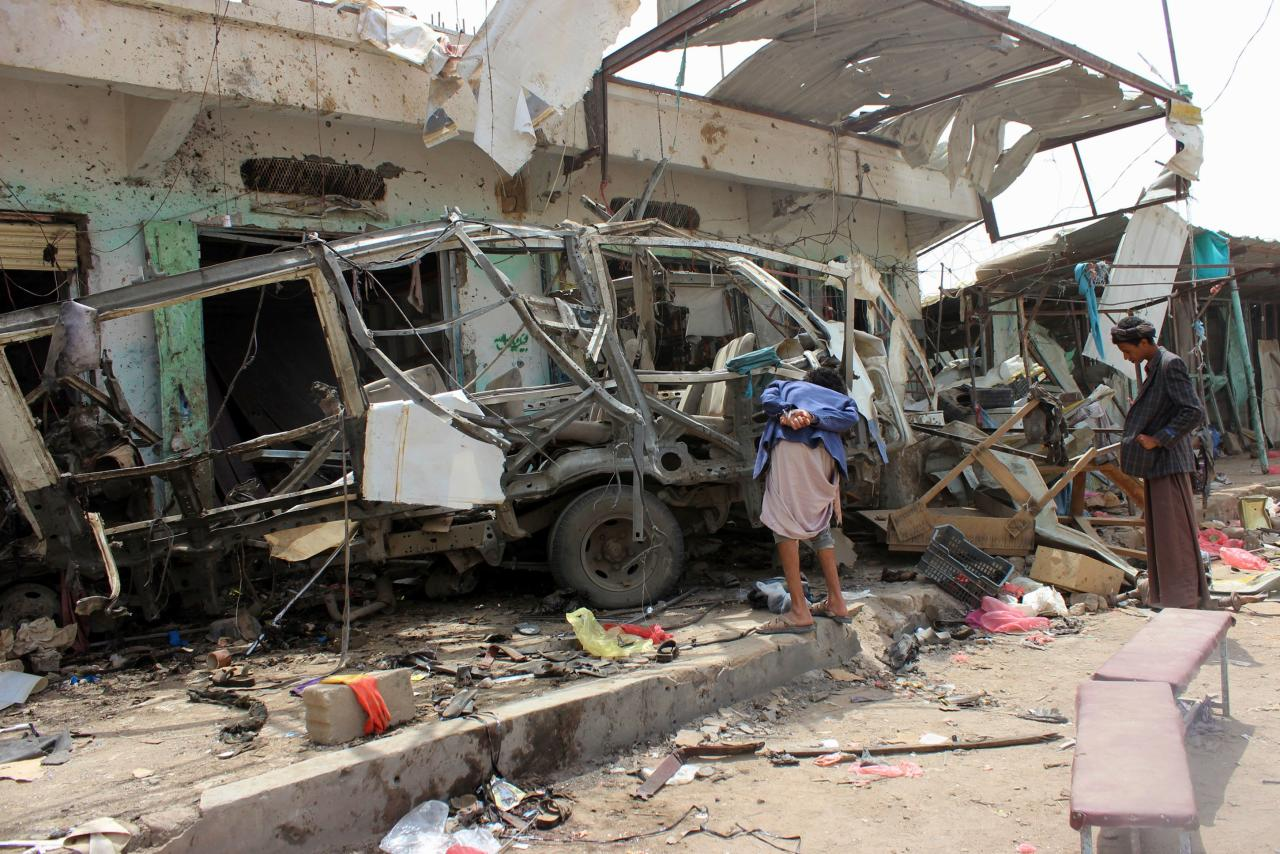 <p>Yemenis gather next to the destroyed bus at the site of a Saudi-led coalition air strike, that targeted the Dahyan market the previous day in the Huthi rebels' stronghold province of Saada on Aug. 10, 2018. (Photo: Stringer/AFP/Getty Images) </p>