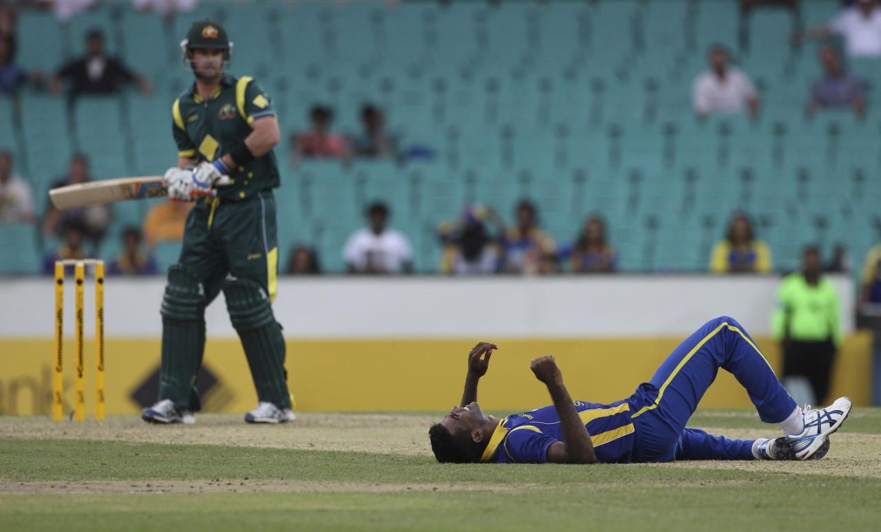 Sri Lanka cricket player Farveez Maharoof, right, lies on the pitch after missing a catch hit by Australia's Daniel Christian during a ODI cricket match against Australia at the Sydney Cricket Ground in Sydney, Australia Friday, Feb. 17, 2012. (AP Photo/Rob Griffith)