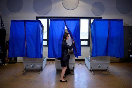 A voter leaves the booth after casting her ballot in the Pennsylvania primary at a polling place in Philadelphia, Pennsylvania, U.S., April 26, 2016. REUTERS/Charles Mostoller/File Photo