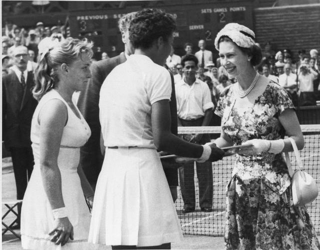 """FILE - In this July 6, 1957 file photo, Queen Elizabeth II, right, presents winners trophy to Althea Gibson who won the women's title in the All England Lawn Tennis Championship at Wimbledon. When the US Open begins this week, she will have a statue unveiled in her honor. Says tennis great Billie Jean King: """"She's our Jackie Robinson of tennis."""" (AP Photo)"""