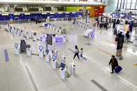 Travelers walk through the nearly empty JetBlue terminal at Logan Airport, Friday Nov. 20, 2020, in Boston. In Massachusetts, the state agency that operates Boston's Logan Airport says it must cut about 25% of its workforce amid a $400 million budget deficit brought on by a steep drop in travel during the pandemic. (AP Photo/Michael Dwyer)