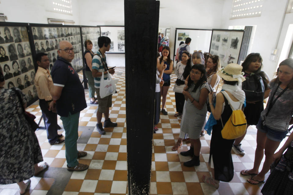 Tourists view portraits of victims executed by the Khmer Rouge regime at the Tuol Sleng Genocide Museum in Phnom Penh, Cambodia on Feb. 5, 2018. Cambodians on Monday, April 12, 2021, continued to condemn an Irish photo restorer for altering photographs of victims of their country's 1970s genocide to show them smiling, saying his decision and that of an international media group to publish them showed horrible judgement.(AP Photo/Heng Sinith)