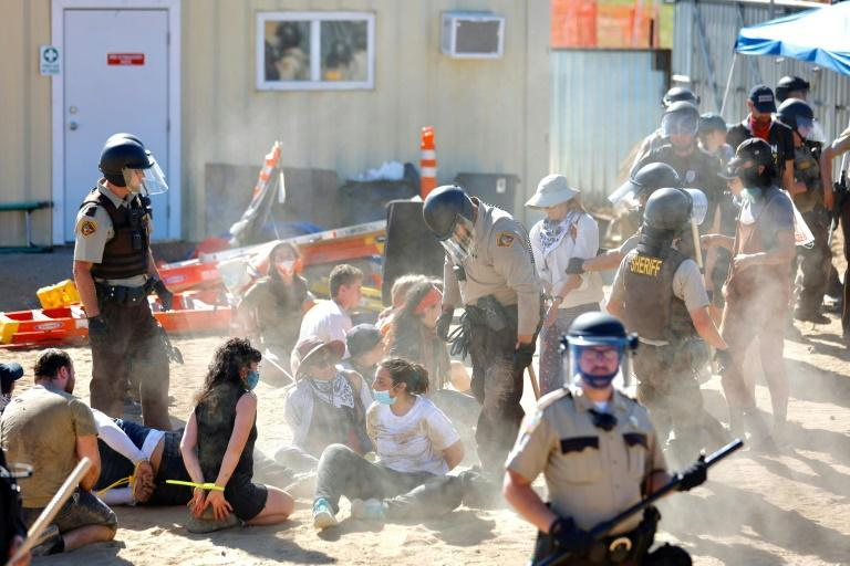 Police in riot gear arrest environmental activists at the Line 3 pumping station on June 7, 2021
