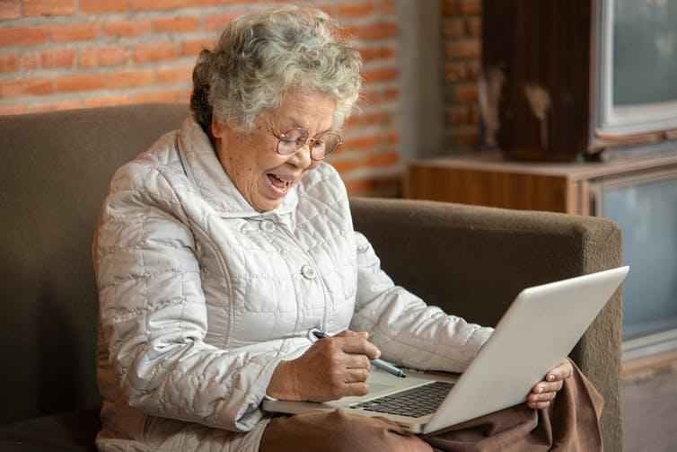 An older black women on her laptop smiling and looking happy.