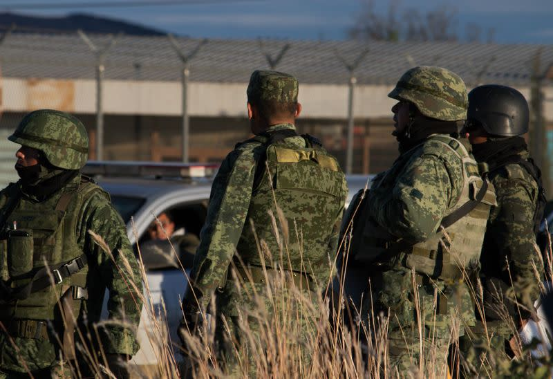 Members of the Mexican National Guard stand guard as they keep watch outside the prison after sixteen inmates were killed and five were wounded in a prison fight at the Regional Center for Social Reintegration in the town of Cieneguillas