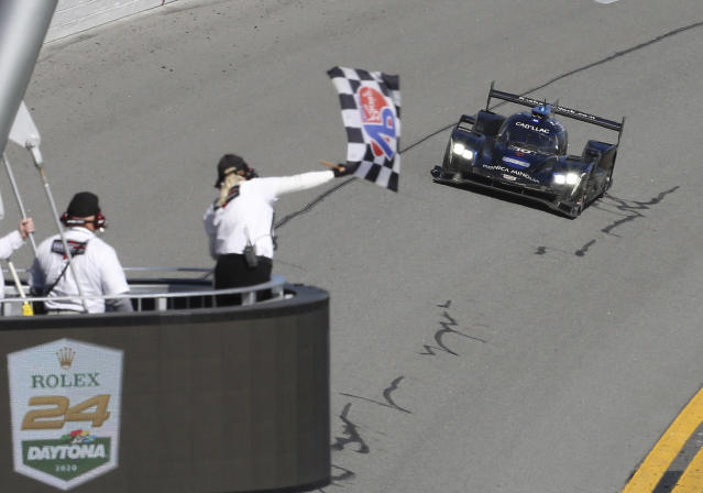 Konica Minolta Cadillac DPi-V.R driver Kamui Kobayashi takes the checkered flag to win the Rolex 24-hour auto race at Daytona International Speedway, Sunday, Jan. 26, 2020, in Daytona Beach, Fla. (AP Photo/David Graham)