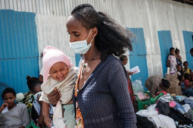 TOPSHOT - An internal displaced mother, who fled the violence in Ethiopia's Tigray region, carries her child as she receives donated items from the citys individuals organized by Self-volunteer Mahlet Tadesse, 27, in Mekele, the capital of Tigray region, Ethiopia, on June 22, 2021. - Mahlet Tadesse, a former business woman now studying masters in socialogy at Mekelle University, supports about 100 women with 155 kids  at Midregenet Elderly Center. She negotiated with the city to transform the public building into an IDP camp to host pregnant or lactating mothers from other IDP camps in inferior conditions two months ago. (Photo by Yasuyoshi CHIBA / AFP) (Photo by YASUYOSHI CHIBA/AFP via Getty Images) (Photo: YASUYOSHI CHIBA via AFP via Getty Images)