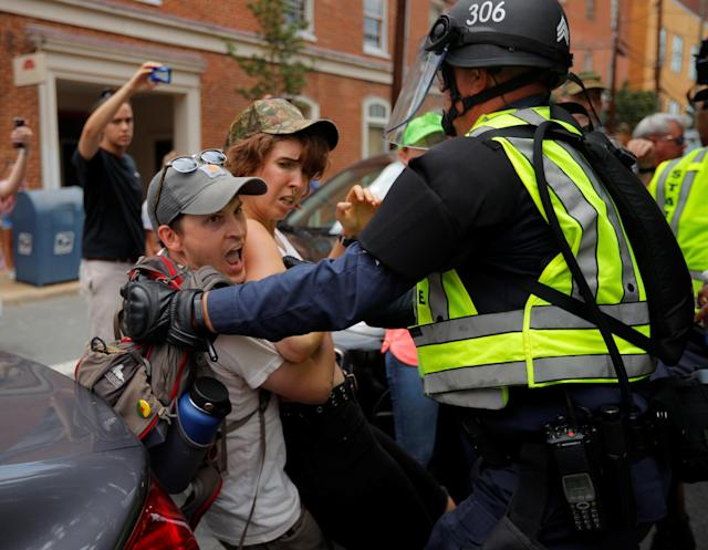 "<p>Police detain a protester at the site where Heather Heyer was killed, on the one year anniversary of the 2017 Charlottesville ""Unite the Right"" protests, in Charlottesville, Virginia, U.S., August 12, 2018. REUTERS/Brian Snyder – RC1D004F6340 </p>"