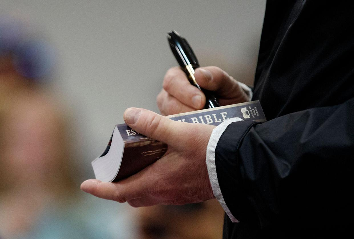 President Trump signs a Bible as he greets people at Providence Baptist Church in Lee County, Ala., on March 8 as he travels to tour areas where tornadoes killed 23 people. (Photo: Carolyn Kaster/AP)