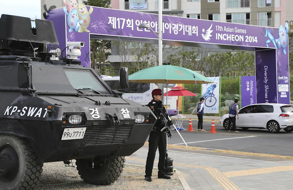 An armed SWAT officer stands guard outside the athletes village for the 17th Asian Games in Incheon, South Korea, Thursday, Sept. 18, 2014. The South Korean west city will host the 17th Asian Games which will be held from Sept. 19 to Oct. 4.(AP Photo/Rob Griffith)