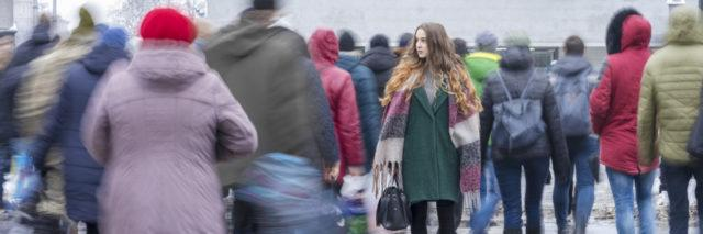 Woman going the opposite direction from a blurry crowd.