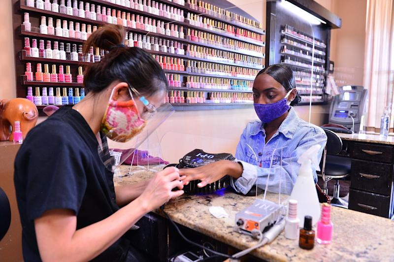 Nail technician Habe is protected by a plexiglass barrier while giving a customer a manicure at Nails and Spa salon on May 20, 2020, in Miramar, Florida. (Johnny Louis via Getty Images)