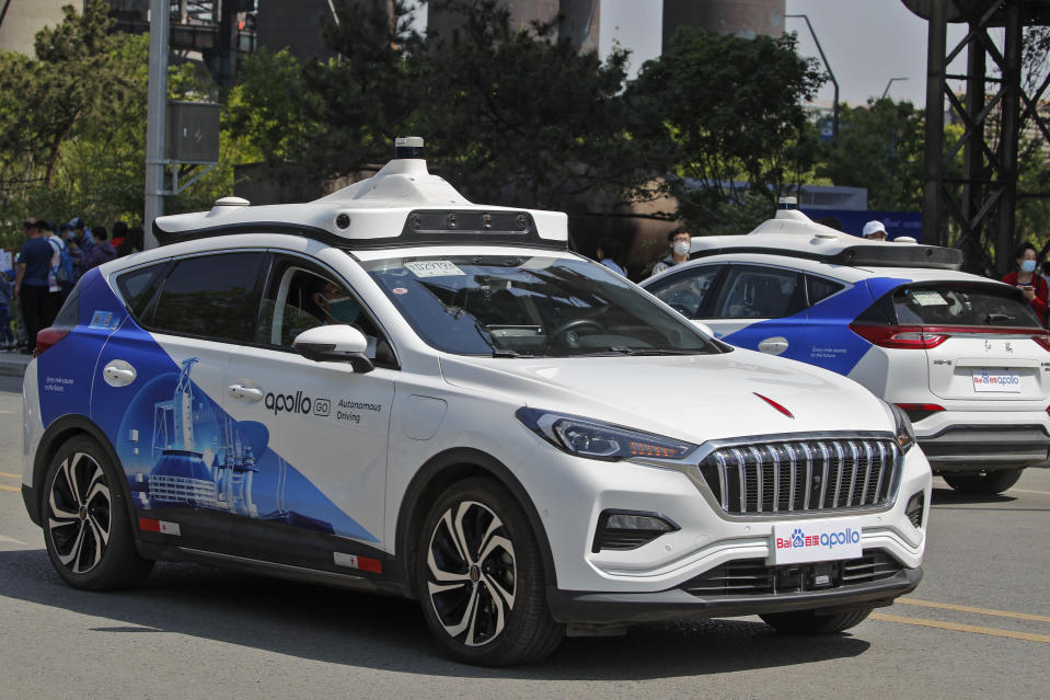 Baidu Apollo Robotaxis move on a street at the Shougang Park in Beijing, Sunday, May 2, 2021. Chinese tech giant Baidu rolled out its paid driverless taxi service on Sunday, making it the first company that commercialized autonomous driving operations in China. (AP Photo/Andy Wong)