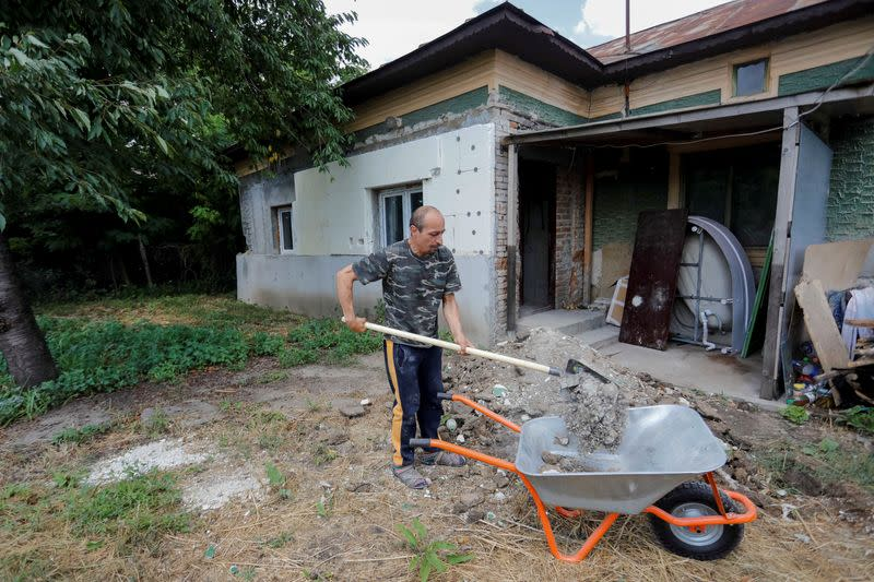 Alberto Gogu uses a shovel to clear debris in his courtyard