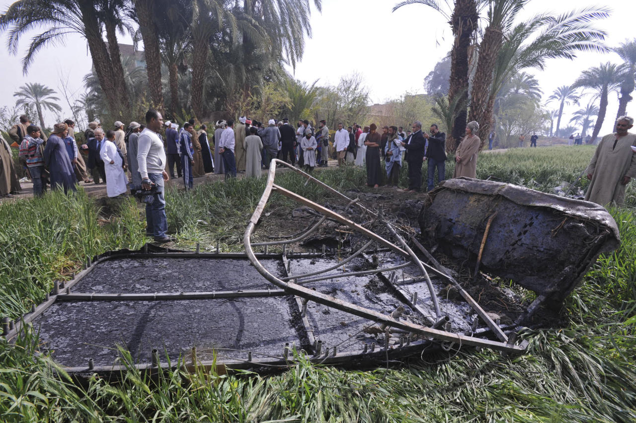 Egyptians gather at the site of a balloon crash where the remains of the burned gondola are seen, outside al-Dhabaa village, just west of the city of Luxor, 510 kilometers (320 miles) south of Cairo, Egypt, Tuesday, Feb. 26, 2013. A hot air balloon flying over Egypt's ancient city of Luxor caught fire and crashed into a sugar cane field on Tuesday, killing at least 18 foreign tourists, a security official said. The casualties included French, British, Belgian, Hungarian, Japanese nationals and nine tourists from Hong Kong, Luxor Governor, Saad told reporters. (AP Photo/Hagag Salama)
