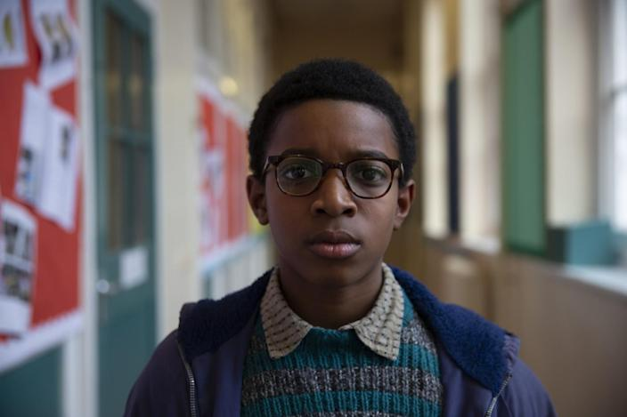 A bespectacled schoolboy in a green and gray knit sweater