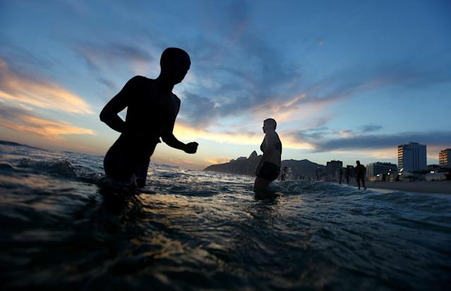 RIO DE JANEIRO, BRAZIL - FEBRUARY 21: People walk through the water on Ipanema Beach on February 21, 2014 in Rio de Janeiro, Brazil. Brazil is ramping up to host the 2014 FIFA World Cup and the Rio 2016 Olympic Games. (Photo by Mario Tama/Getty Images)